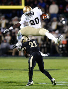 Notre Dame's Cierre Wood (20) leaps over the head of Purdue's Ricardo Allen as he runs the ball downfield during the game at Purdue's Ross-Ade Stadium in West Lafayette on Saturday, October 1, 2011.